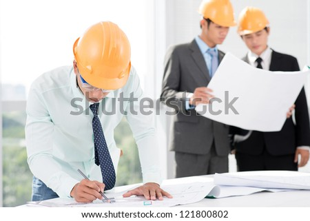 Three architects working on the project blueprints in office - stock photo