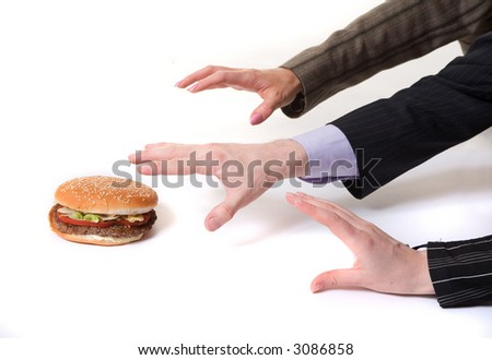 Three arms are drawing to the hamburger. Who is the leader? Hunger in the office. - stock photo