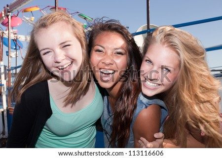 Three Asian and white teenage friends laughing together - stock photo