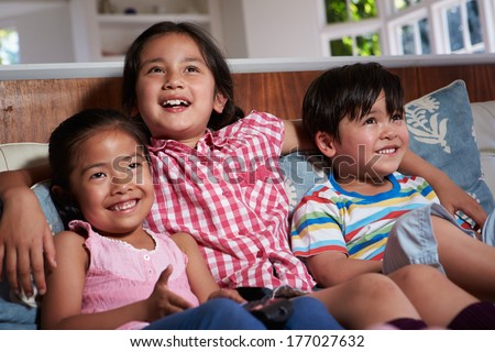 Three Asian Children Sitting On Sofa Watching TV Together - stock photo