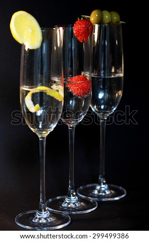 Three assorted cocktails with garnish against a black backdrop - stock photo