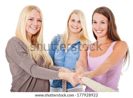 Three attractive girls pulling heavy rope. All on white background.  - stock photo