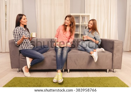 Three attractive girls sitting on sofa with cups of tea and laughing - stock photo
