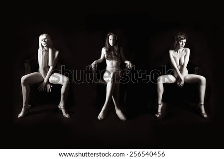 Three attractive nude models in front of dark studio background, their private parts are not visible, monochrome photo - stock photo