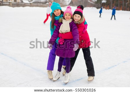 three attractive skater girl hug each other on the ice of the frozen lake with kids on the background
