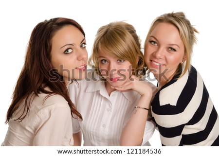 Three attractive smiling young women friends standing close together looking up at the camera isolated on white - stock photo