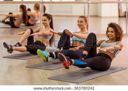 Three attractive sport girls smiling while doing abs lying on yoga mat in fitness class - stock photo