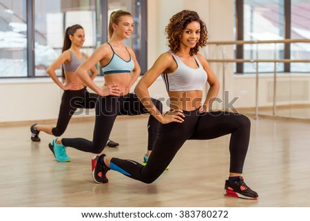 Three attractive sport girls smiling while doing lunges in fitness class. Beautiful Afro-American girl looking at camera - stock photo