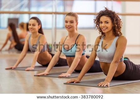 Three attractive sport girls smiling while stretching the body lying on yoga mat in fitness class - stock photo