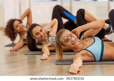 Three attractive sport girls smiling while working out lying on yoga mat in fitness class. Beautiful blonde girl looking at camera - stock photo
