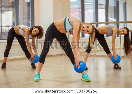 Three attractive sport girls smiling while working out with fitness ball and bending in fitness class - stock photo