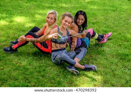 Three attractive sporty females sitting on a lawn and doing selfie after fitness workouts.