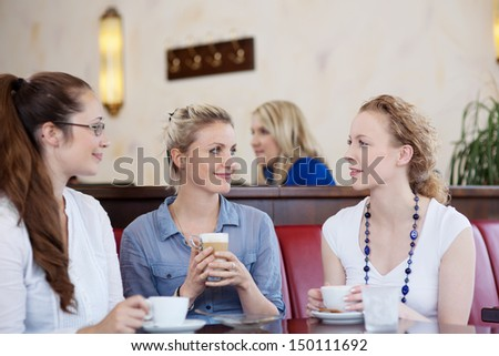Three attractive stylish young female friends drinking coffee together and chatting in a cafe - stock photo