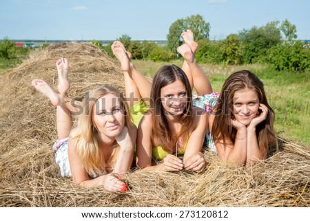 Three attractive women laying on hay stack - stock photo
