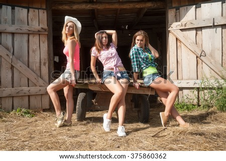 Three attractive women sitting on cart in front of stable entrance