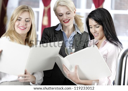 Three attractive work colleagues reading a wine list.