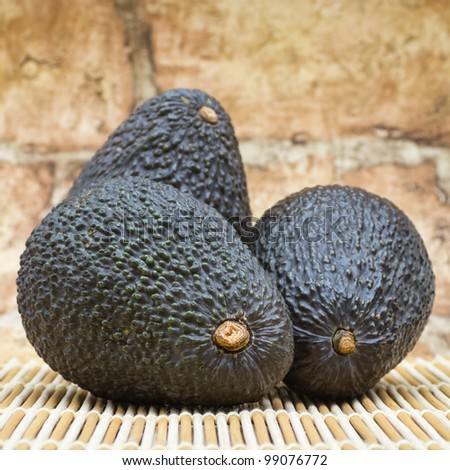 Three avocados on mat against brick wall background - stock photo