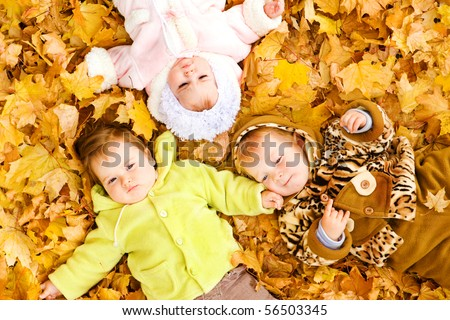 Three baby friends lying on the  autumn leaves - stock photo