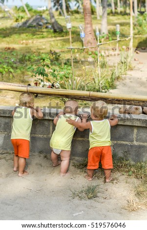 Three baby Toddler looking through fence on the hens and roosters in the henhouse. The yellow shirts. Two boys and one girl