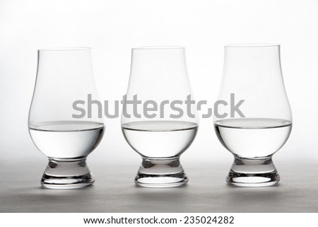 Three backlit crystal glasses containing vodka, gin, moonshine, or tequila. - stock photo