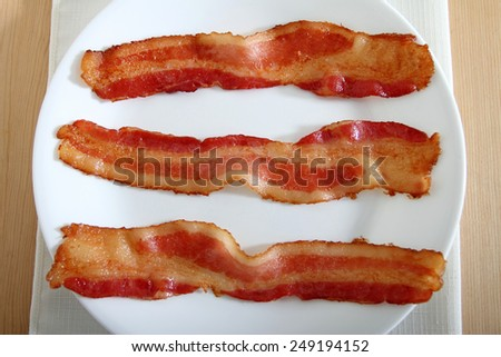 Three bacon strips on a white plate - stock photo