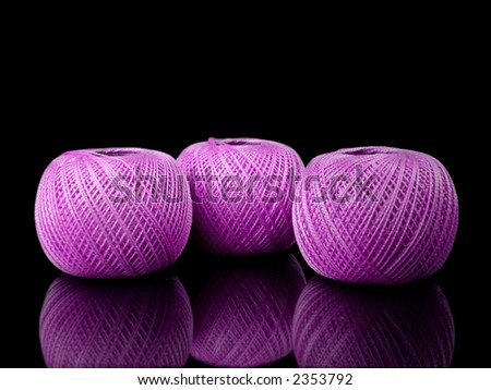 three balls of pink string on a black background with reflection