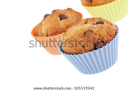 Three Banana Chocolate Chip muffins in colourful silicone cases. Room for your text. - stock photo