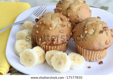 Three banana nut muffins served with bananas - stock photo