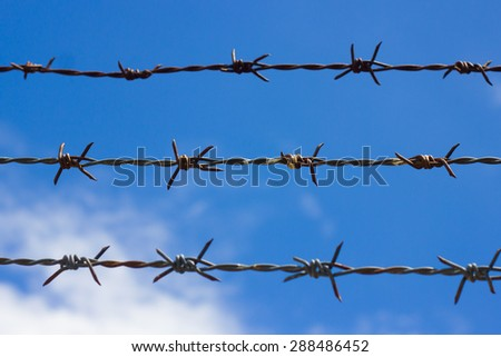 three barbed Wire on white cloud blue sky