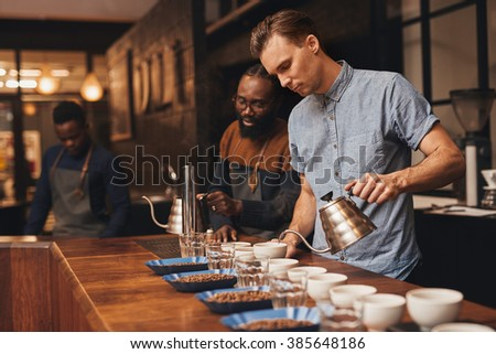Three baristas at work in a modern roastery preparing for a coffee tasting, with rows of cups, water glasses and open containers of a variety of roasted beans - stock photo