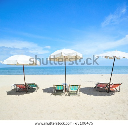 Three beach chairs with umbrellas - stock photo