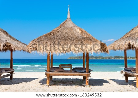 Three beach house on a tropical beach coast near blue sea - stock photo