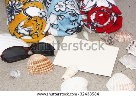 three beach towels in the sand, sunglasses, blank postcard and seashells