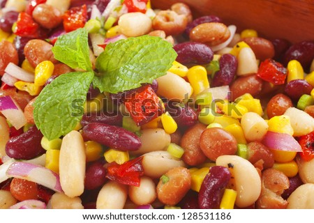 Three bean salad with sweetcorn, roasted red peppers and red onion in a vinaigrette dresing. - stock photo
