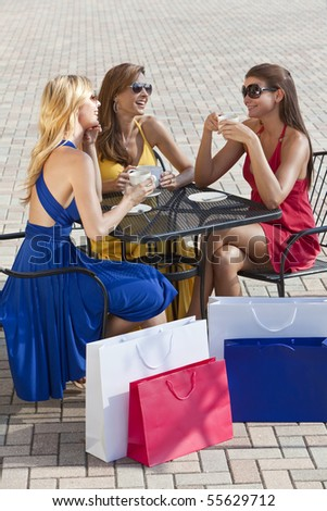 Three beautiful and sophisticated young women friends wearing sunglasses and having coffee around a modern city cafe table surrounded by shopping bags - stock photo