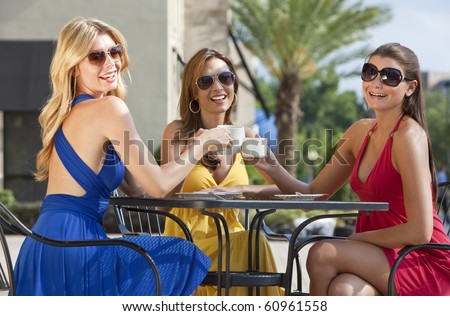 Three beautiful and sophisticated young women friends wearing sunglasses and having coffee around a modern city cafe table