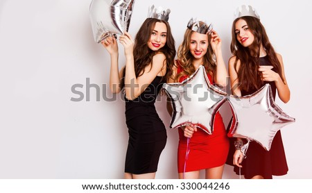 Three beautiful elegant women celebrate birthday  and dancing. Best friends wearing black stylish evening dress, high heel shoes ,crown on head .Bright make up, red lips. Inside. - stock photo