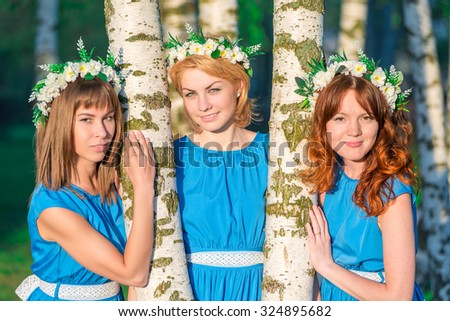 Three beautiful girlfriends about birch trees on a summer evening - stock photo