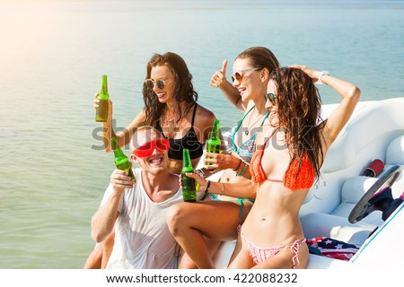 Three beautiful girls and a guy in funny glasses drinking beer near the speed boat, on the beach, sexy bikini, fashion accessories, merry company, happy, crazy emotions, pretending grimaces, laughs - stock photo