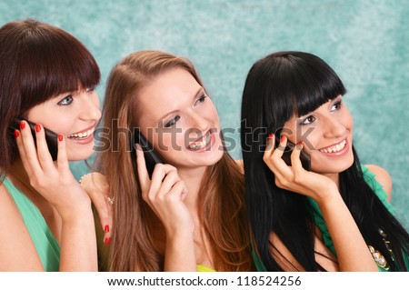three beautiful girls in green dresses on a green with a mobile phone - stock photo