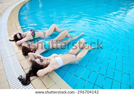 Three beautiful girls in swimsuits lying in a pool of water on vacation