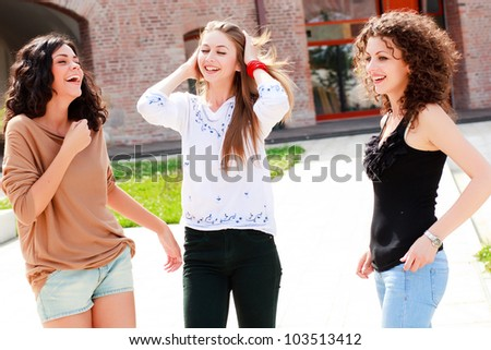 three beautiful girls laughing and having fun - stock photo