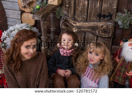 Three beautiful girls posing in Christmas decorations. Girls greet the new year.