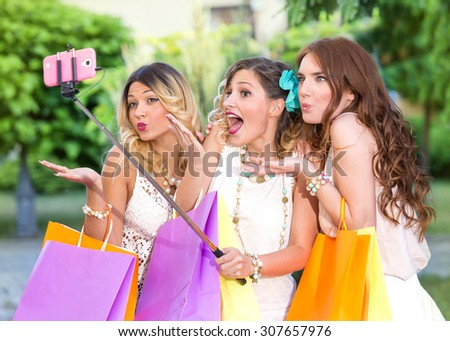 Three beautiful girls with shopping bags taking a selfie with selfie stick. Shopping concept. Lens Flare