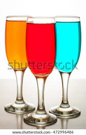 Three beautiful glasses of champagne with colored liquids on white background