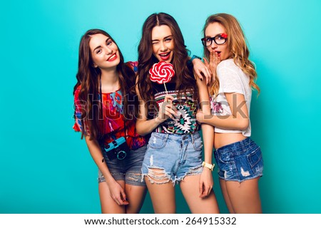 Three beautiful happy sexy women in stylish trendy  summer outfit posing against  blue  wall .Pretty girl holding   lolly-pop and her friends wearing stylish funky sunglasses and retro film camera. - stock photo