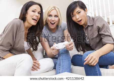 Three beautiful interracial young women friends at home having fun playing video console games together and laughing - stock photo