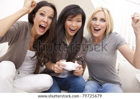Three beautiful interracial young women friends at home having fun playing video games together and laughing - stock photo