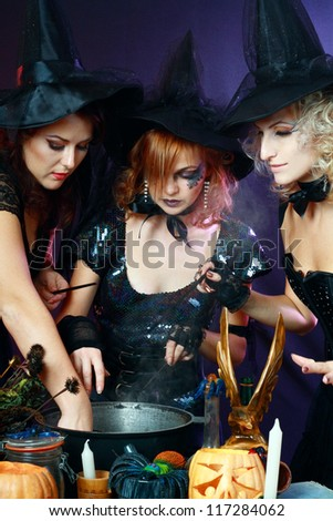 Three beautiful sexy charming halloween witches making potion - stock photo