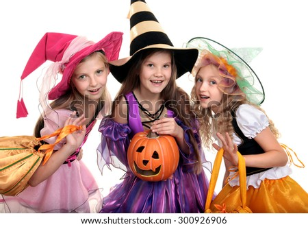 Three Beautiful Smiling Little Girls with Long Hair in the Colorful Witch Costume Looking at Camera with Trick or Treat Bags and Jack O' Lantern.
